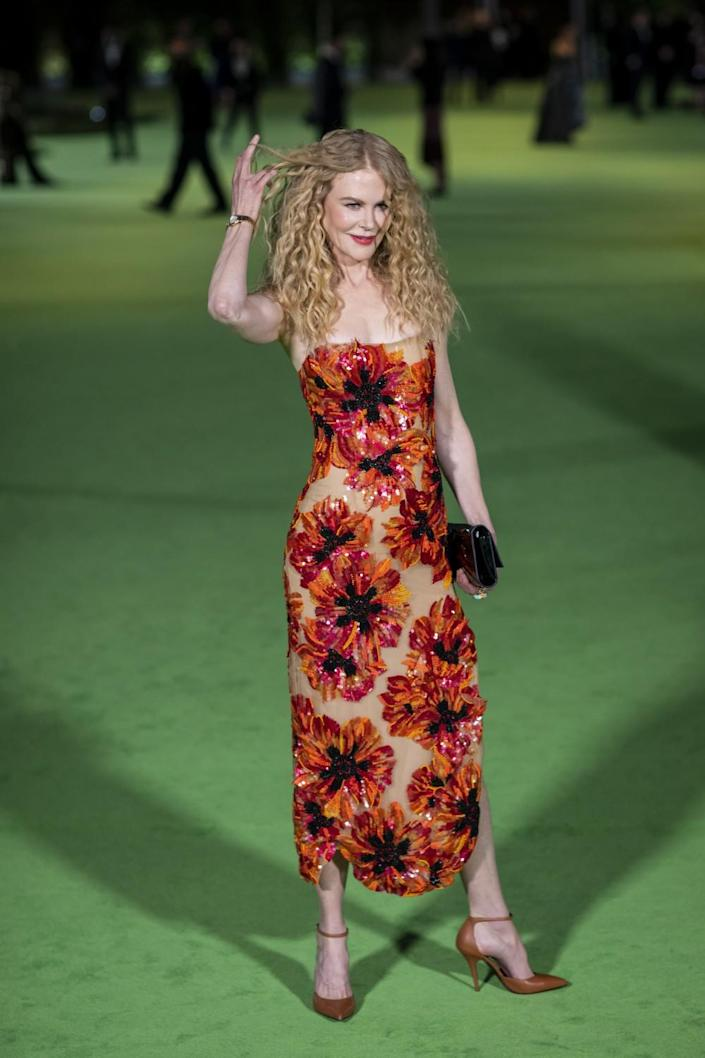 A woman in an orange, floral dress posing on a green carpet