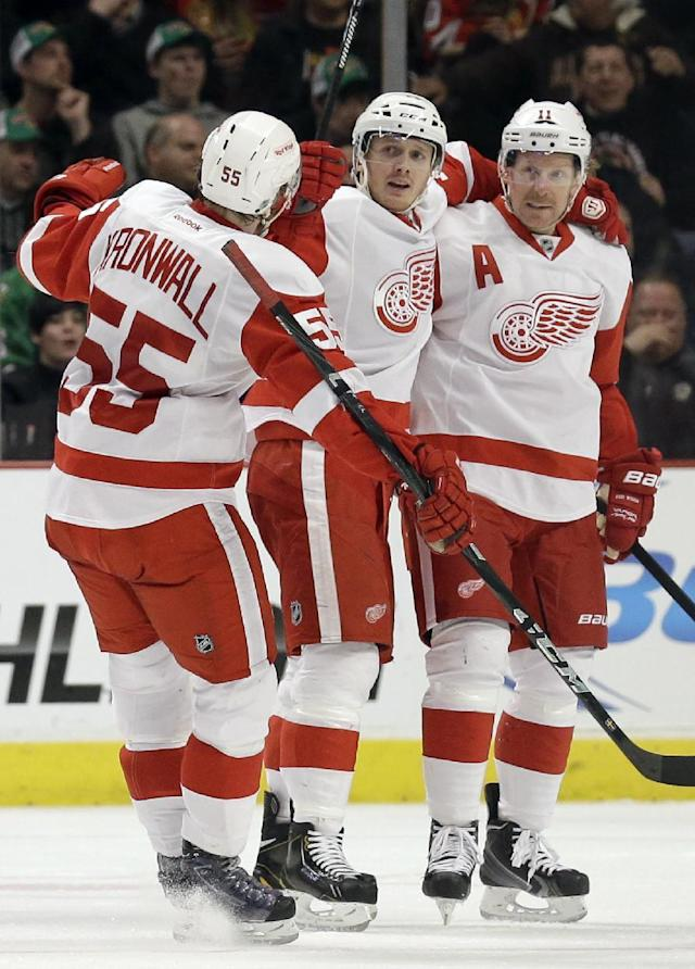 Detroit Red Wings' Gustav Nyquist (14), center, celebrates with Niklas Kronwall (55), left, and Daniel Alfredsson (11) after scoring his goal during the second period of an NHL hockey game against the Chicago Blackhawks in Chicago, Sunday, March 16, 2014. (AP Photo/Nam Y. Huh)