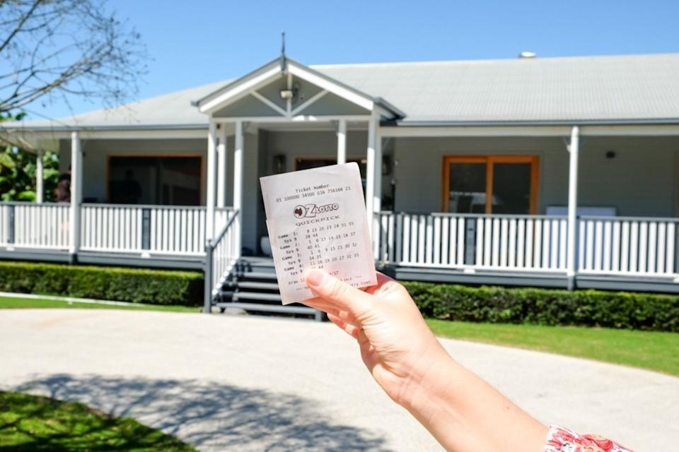 Woman holds oz lotto ticket in front of home. Source: The Lott
