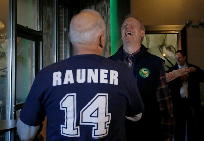 Republican gubernatorial primary candidate Bruce Rauner, right, laughs at a story told to him by campaign volunteer Rod Spears, during a campaign stop Monday, March 17, 2014, in Edwardsville, Ill. Rauner faces State Sen. Bill Brady, State Sen. Kirk Dillard and State Treasurer Dan Rutherford in Tuesday's primary. (AP Photo/Charles Rex Arbogast)