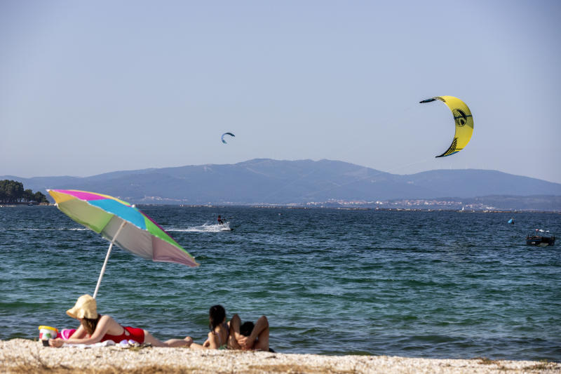 PONTEVEDRA, SPAIN - JULY 21: People practice windsurfing on the beach of O Bao on July 21, 2020 in Pontevedra, Spain. The island of Arosa, Arousa in the Galician language, has an area of approximately 7 square kilometers. It has 36 kilometers of coastline, of which 11 are beach, with fine white sand. It is one of the tourist destinations in Galicia with the most influx of visitors. (Photo by Xurxo Lobato/Getty Images)