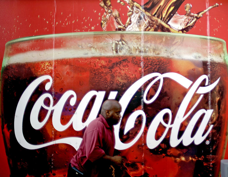 FILE- In this Monday, July 16, 2012, photo, a billboard for Coca Cola is seen outside a convenience store in Atlanta. The Coca-Cola Co. says its net income slipped in the second quarter from a year ago, as rising costs for ingredients offset its expansion overseas. The world's biggest beverage maker, which makes Minute Maid, Powerade and Dasani, says revenue growth was powered by higher prices in the U.S. and expansion in emerging markets such as India, where volume rose 20 percent.(AP Photo/David Goldman)