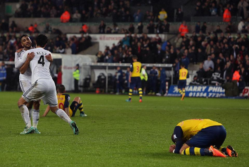 Swansea City's Neil Taylor (L) and Ki Sung-Yueng (2L) celebrate at the final whistle as Arsenal's Alex Oxlade-Chamberlain (R) lies on the ground after Swansea won the English Premier League football match on November 9, 2014 (AFP Photo/Geoff Caddick)