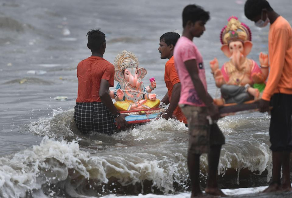 """<div class=""""paragraphs""""><p> Volunteers immerse idols of god Ganesha in the Arabian Sea on the 5th day during the Ganesh Chaturthi festival, at Dadar Chowpatty in Mumbai, Tuesday, 14 September.</p></div>"""