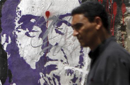 A man walks past graffiti depicting the Deputy Guide of the Muslim Brotherhood Shater in downtown Cairo