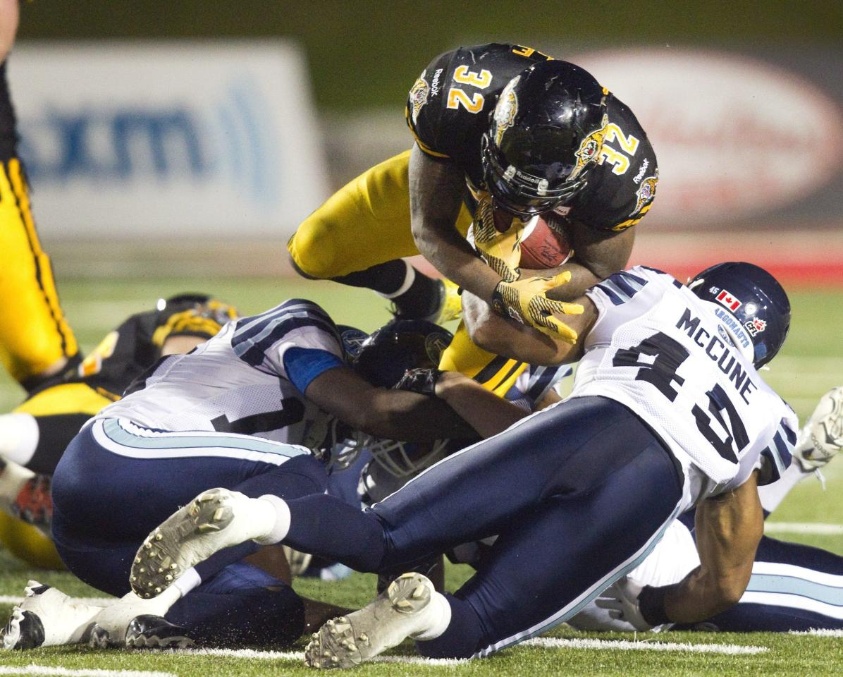 Hamilton Tiger-Cats C.J. Gable (top) dives over Toronto Argonauts Robert McCune for a first down in the second half of their CFL football game in Guelph October 14, 2013. REUTERS/Fred Thornhill (CANADA - Tags: SPORT FOOTBALL)