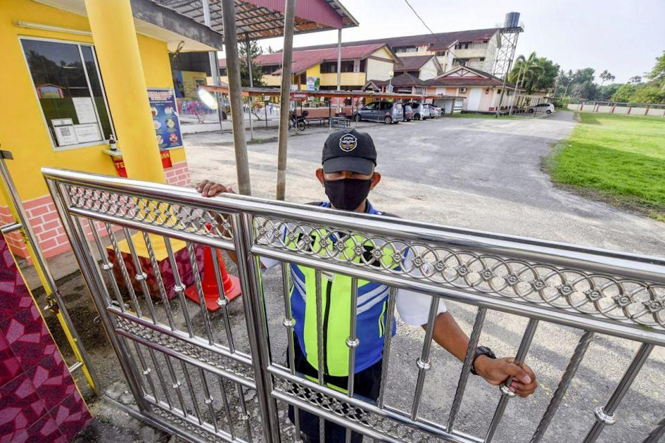 A security guard at Sekolah Kebangsaan Pasir Hor closes the school gate in Kota Bharu April 18, 2021. — Bernama pic