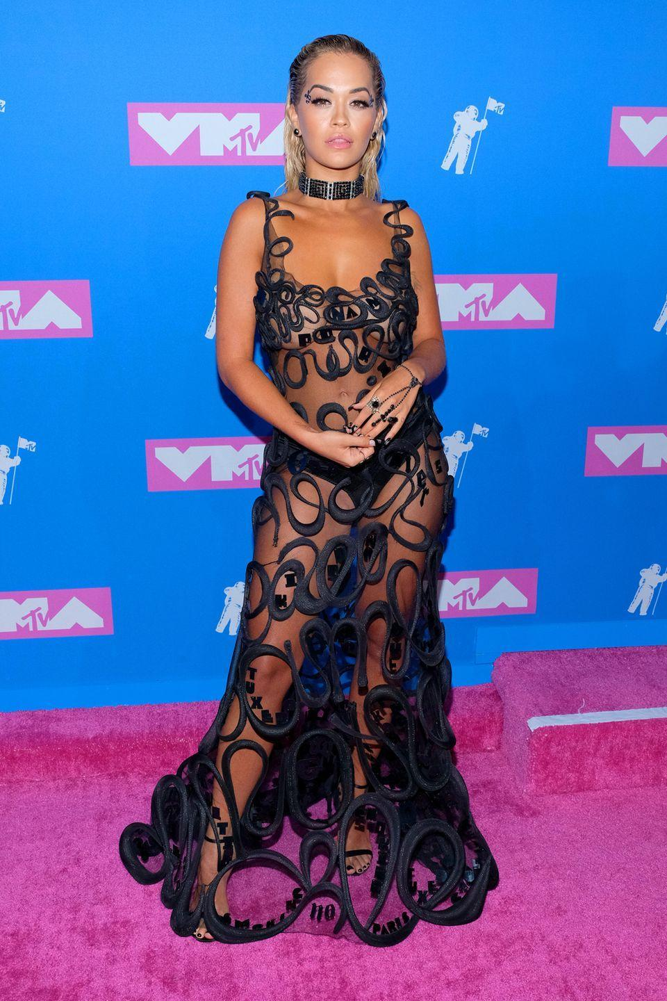 <p>Rita Ora, meanwhile, wore the dress version of our notepad that we take to meetings, with her black pants on show.</p>