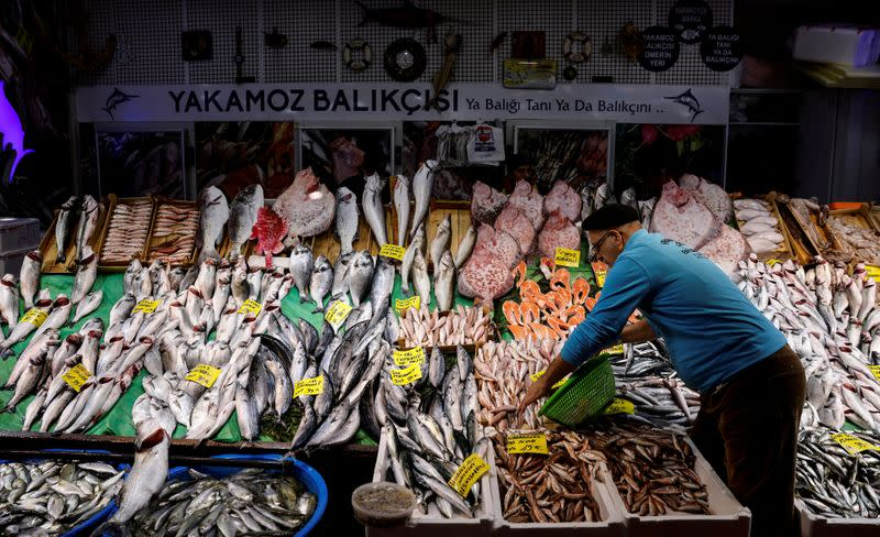 FILE PHOTO: People shop at a fish market at Karakoy district in Istanbul