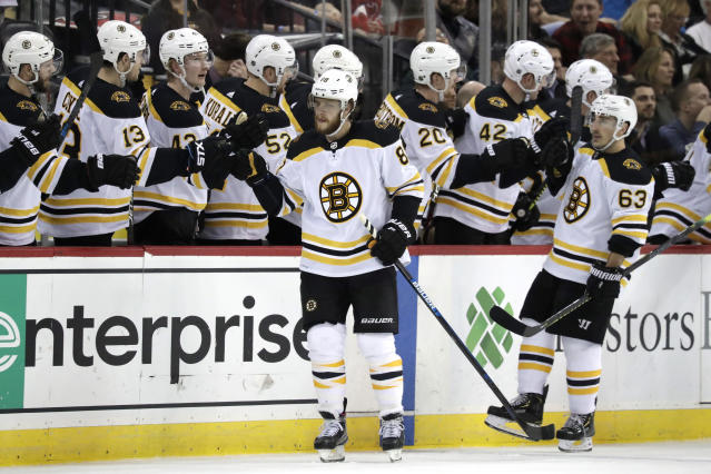 Boston Bruins right wing David Pastrnak, center front, of the Czech Republic, skates by his bench after scoring a goal against the New Jersey Devils during the second period of an NHL hockey game Thursday, March 21, 2019, in Newark, N.J. (AP Photo/Julio Cortez)
