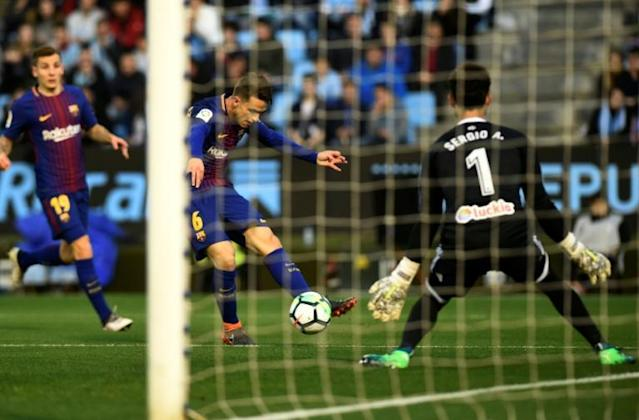 Barcelona's Denis Suarez (C) shoots at the goal guarded by Celta Vigo's Sergio Alvarez at the Balaidos stadium in Vigo on April 17, 2018