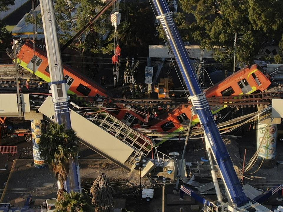 An aerial view of subway cars dangling at an angle from a collapsed elevated section of the Metro line.