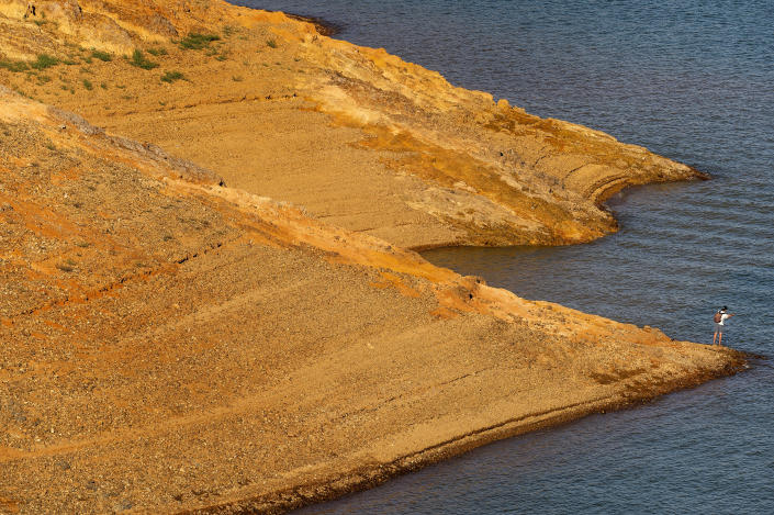 A man fishes on the banks of Shasta Lake on Sunday, May 23, 2021, in Shasta Trinity National Forest, Calif. The reservoir is at 45 percent of capacity and 52 percent of its historical average. (AP Photo/Noah Berger)