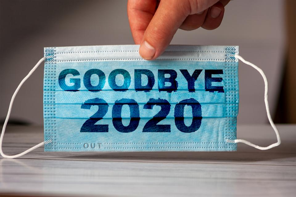The hand holds a medical and protective mask with the word GOODBYE 2020. Concept of coronavirus quarantine. Prevent or stop the spread of the COVID-19 worldwide.