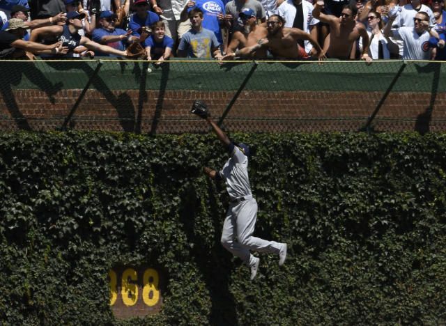 Milwaukee Brewers center fielder Lorenzo Cain (6) can't catch a ball hit for a home run by Chicago Cubs' Jason Heyward (22) during the first inning of a baseball game, Friday, Aug. 2, 2019, in Chicago. (AP Photo/David Banks)