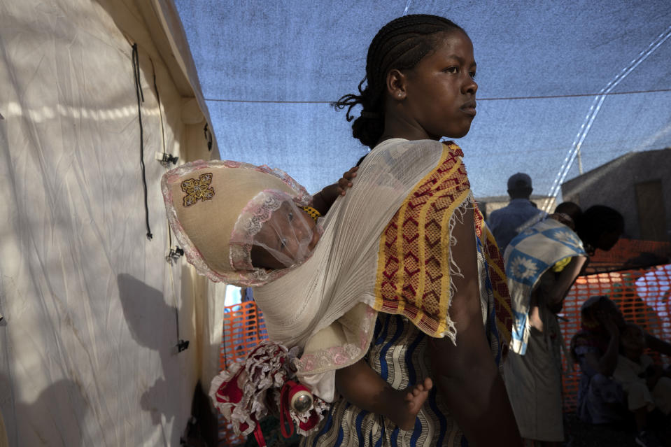 A Tigrayan refugee mother carries her child as she waits her turn for treatment at a clinic run by Doctors Without Borders in Village 8, the transit center near the Lugdi border crossing, eastern Sudan, Tuesday, Dec. 8, 2020. (AP Photo/Nariman El-Mofty)