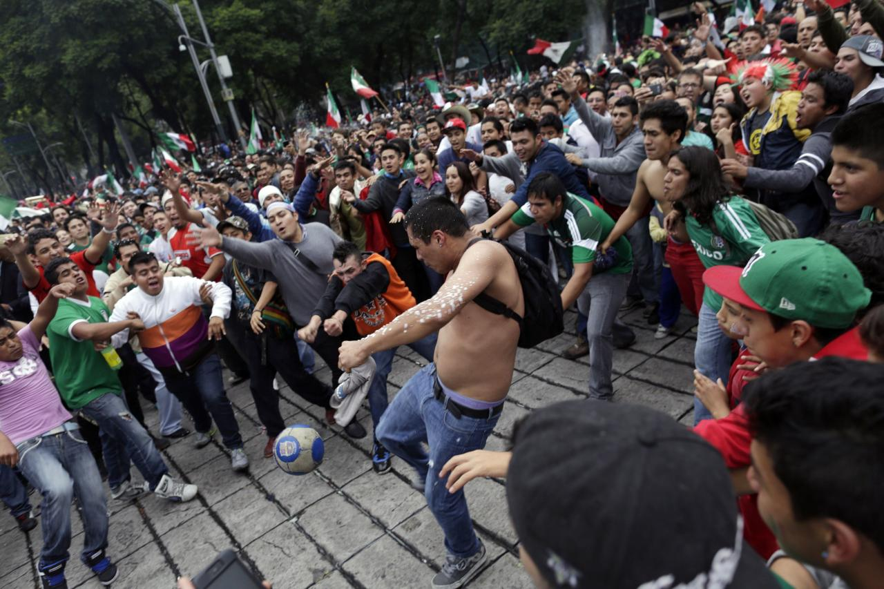 A man kicks a soccer ball as he and other fans celebrate Mexico's victory over Croatia in their 2014 World Cup soccer match, at the Angel of Independence monument in Mexico City June 23, 2014. REUTERS/Carlos Jasso (MEXICO - Tags: SOCIETY SPORT SOCCER WORLD CUP)