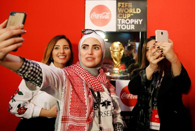 Football fans pose for photographs during the Fifa World Cup Trophy Tour, in Amman, Jordan February 20, 2018. REUTERS/Muhammad Hamed