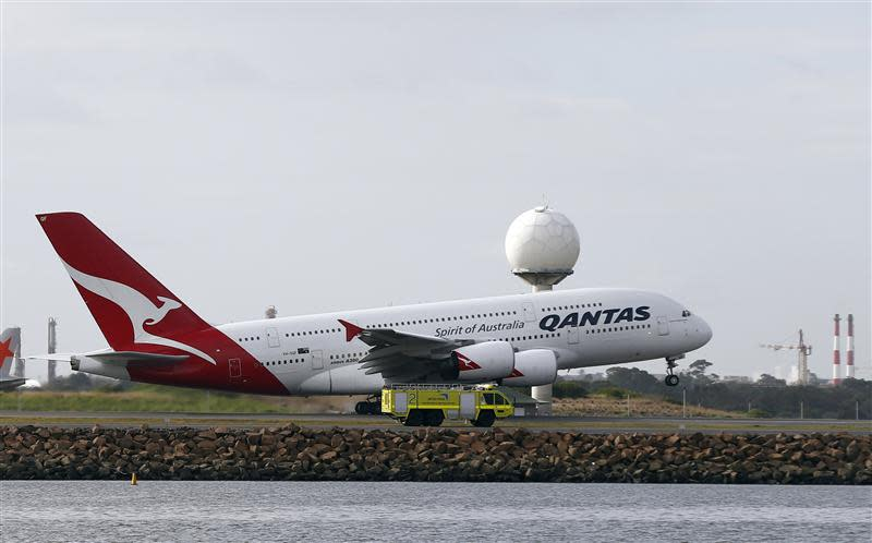 A Qantas plane A380 passes an emergency vehicle as it takes off from Kingsford Smith International airport in Sydney
