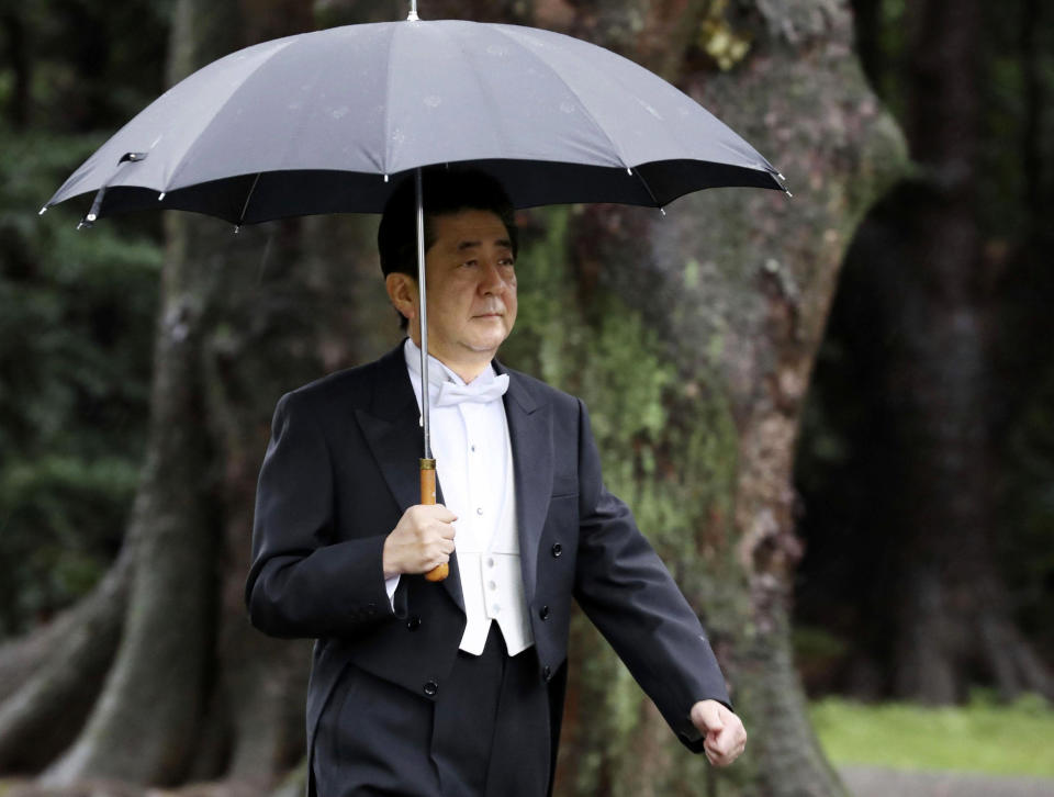 """Japan's Prime Minister Shinzo Abe arrives for the ceremony at """"Kashikodokoro"""", one of three shrines at the Imperial Palace, in Tokyo, Tuesday, Oct. 22, 2019. Emperor Naruhito and Empress Masako visited three Shinto shrines at the Imperial Palace before Naruhito proclaims himself Japan's 126th emperor in an enthronement ceremony. (Kyodo News via AP)"""