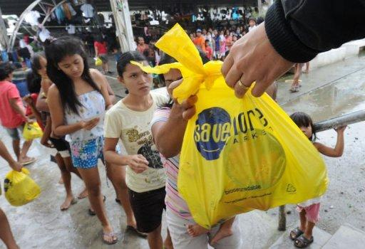 Evacuees receive relief goods from a supermarket in Manila