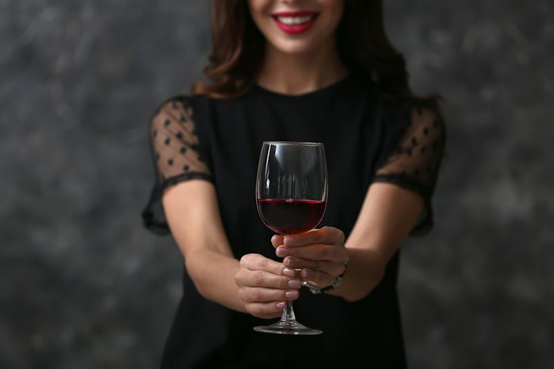 Beautiful young woman with glass of wine on dark background