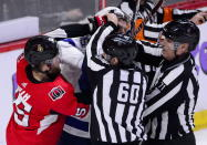 Linesmen try to get between Ottawa Senators left wing Zack Smith (15) and Tampa Bay Lightning defenseman Braydon Coburn (55) during first-period NHL hockey game action in Ottawa, Ontario, Monday, April 1, 2019. (Sean Kilpatrick/The Canadian Press via AP)