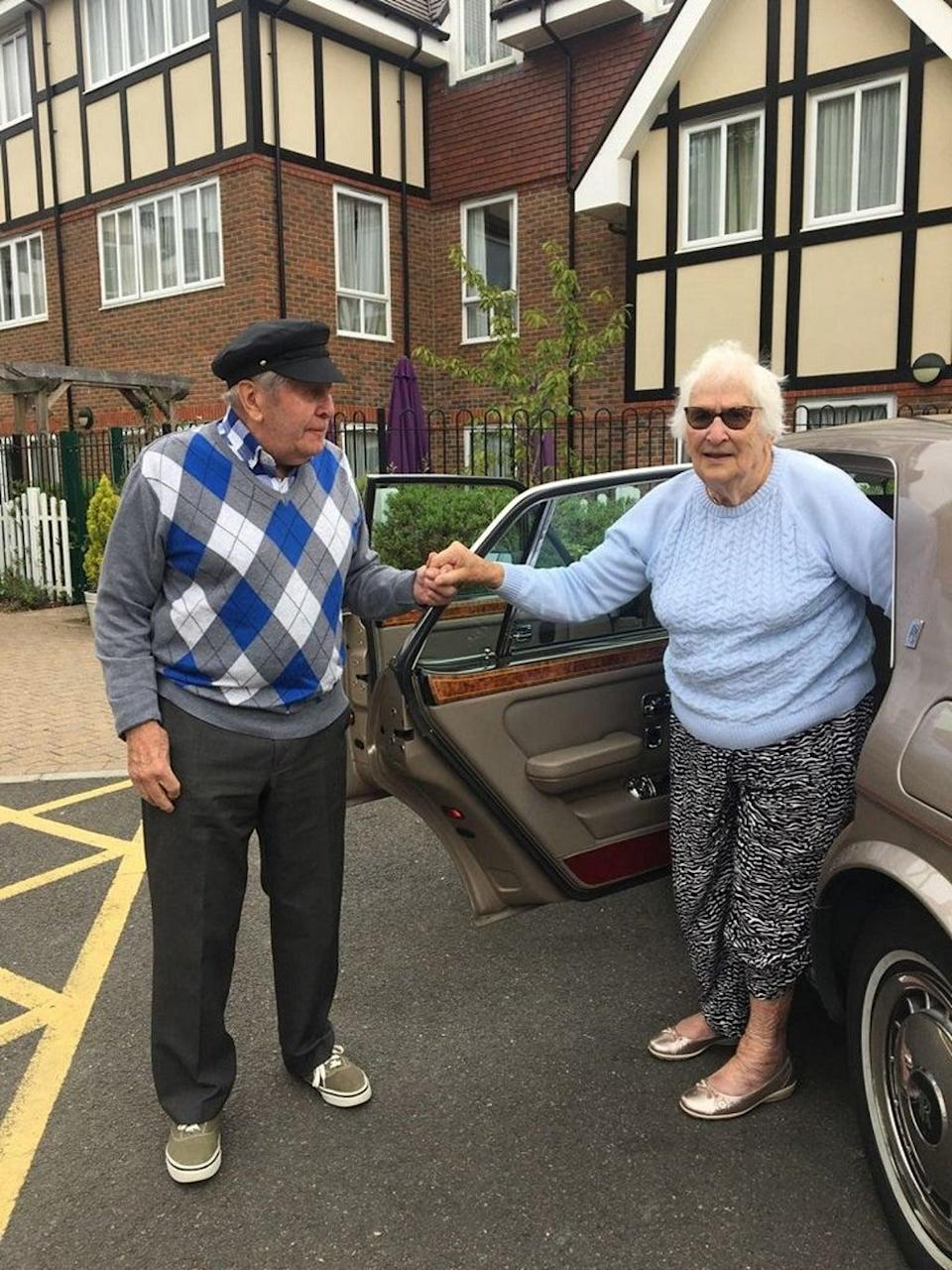 Alec Goy helping fellow resident Eve out of the Rolls Royce (Care UK's Weald Heights/PA).