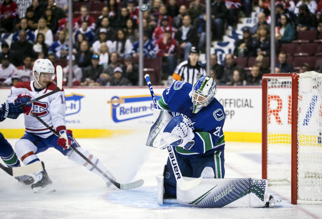 Vancouver Canucks goalie Jacob Markstrom, right, of Sweden, makes a blocker save as Montreal Canadiens' Max Domi, back left, reaches for a possible rebound during the first period of an NHL hockey game in Vancouver, British Columbia, Saturday, Nov. 17, 2018. (Darryl Dyck/The Canadian Press via AP)
