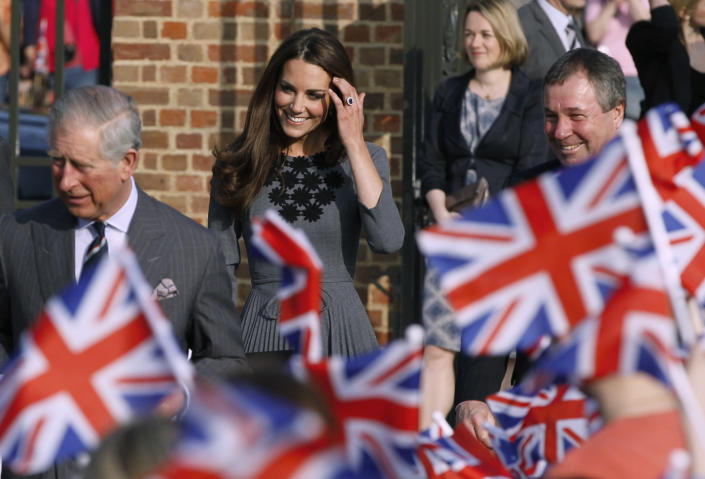 Kate Duchess of Cambridge, center, arrives with Prince Charles, left, and Camilla Duchess of Cornwall, unseen, at the Dulwich Picture Gallery, London to meet school children participating in 'Great Art Quest' a project run by The Prince's Foundation for Children and the Arts Thursday, March, 15, 2012. (AP Photo/Alastair Grant)