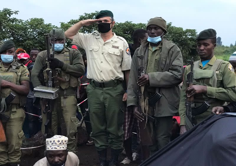 Virunga National Park Rangers and Park director Emmanuel Demerode salutes as they attend the burial of Burhani Abdou Surumwe in Goma