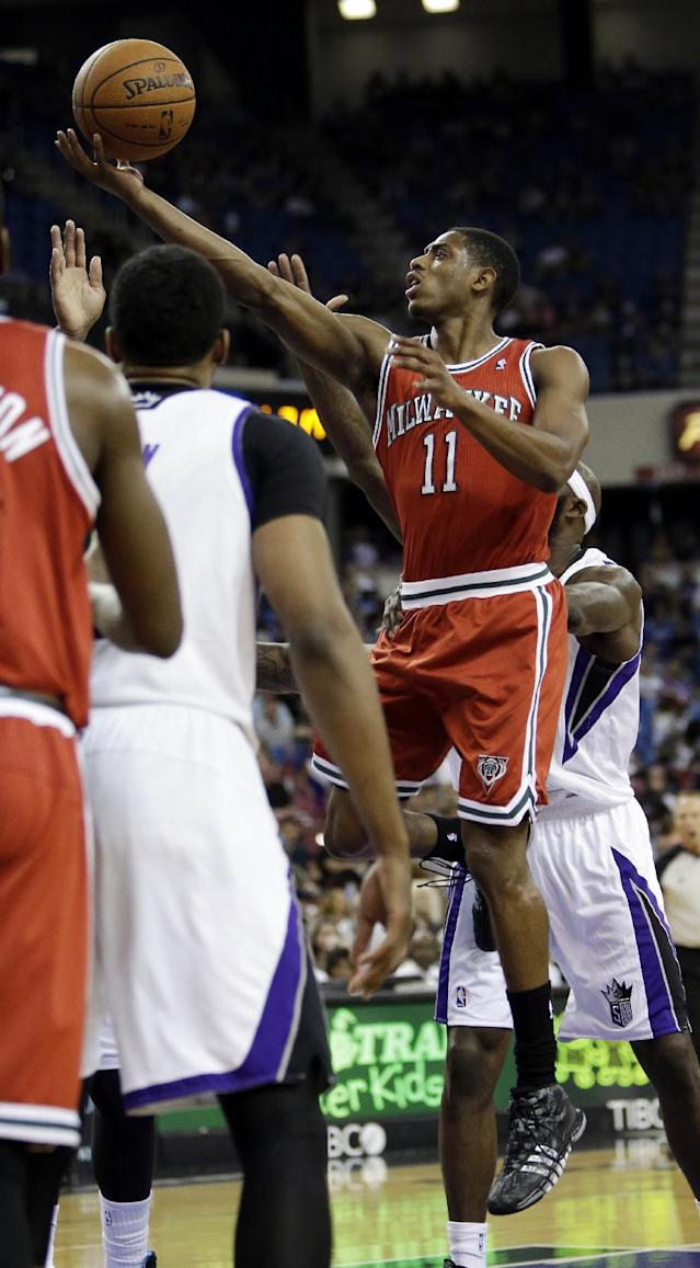 Milwaukee Bucks guard Brandon Knight, center, drives to the basket between Sacramento Kings' Rudy Gay, left, and Reggie Evans, right, during the first quarter of an NBA basketball game in Sacramento, Calif., Sunday, March 23, 2014. (AP Photo/Rich Pedroncelli)
