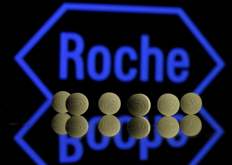FILE PHOTO: Roche tablets are seen positioned in front of a displayed Roche logo in this photo illustration