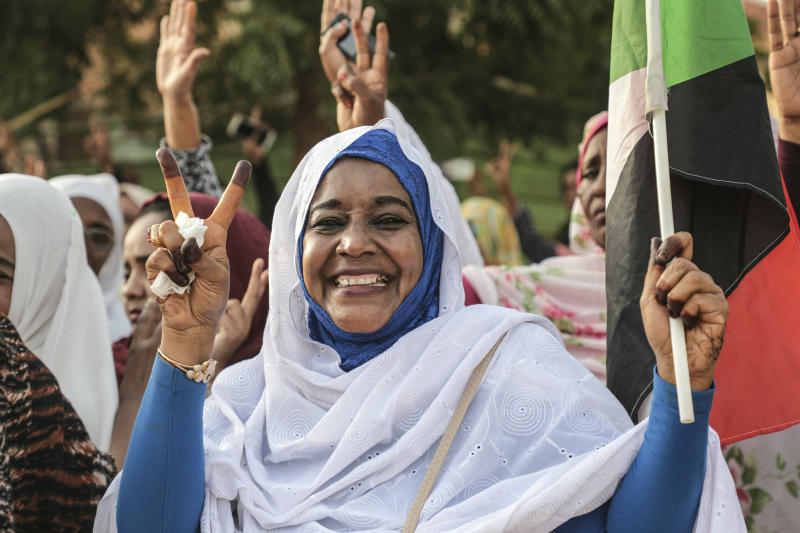 A Sudanese woman celebrates in the streets of Khartoum after ruling generals and protest leaders announced they have reached an agreement on the disputed issue of a new governing body on Friday, July 5, 2019.   The deal raised hopes it will end a three-month political crisis that paralyzed the country and led to a violent crackdown that killed scores of protesters.  (AP Photo)