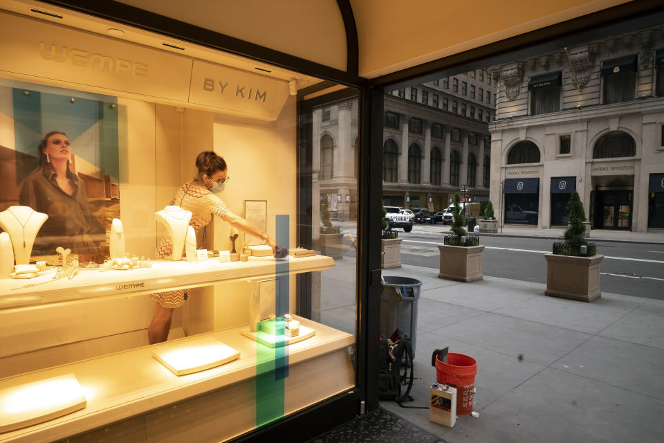 A Wempe store employee places jewellery in a store window, Thursday, June 11, 2020, in New York's Fifth Avenue shopping district. The jeweler is open for in-store and curbside pickup. In the virus times, the near-term and maybe even longer-term impact is undoubtedly going to be ugly. Job losses have been racking up, businesses facing bankruptcy, cultural institutions going under, entire industries like restaurants forced to reconsider everything they do. (AP Photo/Mark Lennihan)