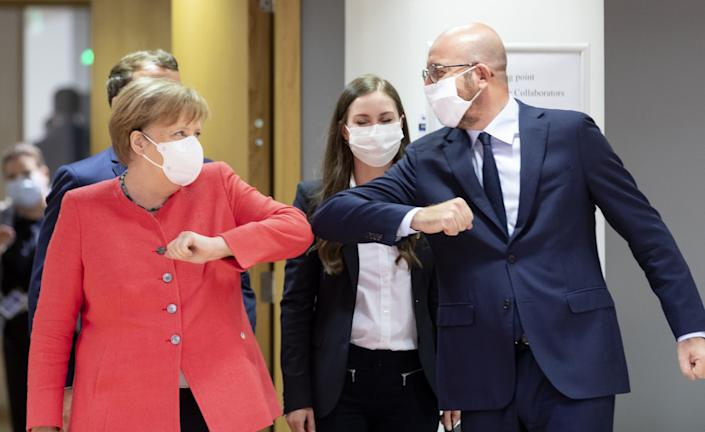 German Chancellor Angela Merkel (L) elbow bumps the President of the European Council Charles Michel (R) during an EU summit on July 17, 2020 in Brussels, Belgium - Thierry Monasse / Getty