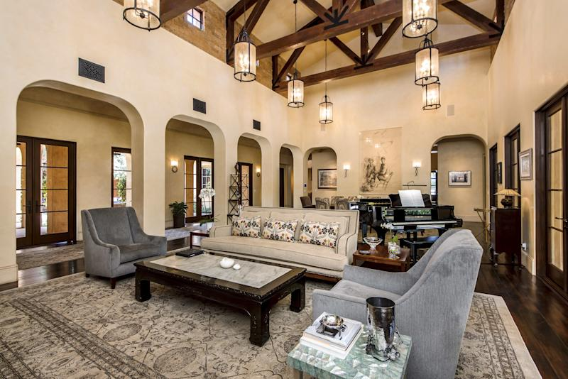 The living and dining room also has high ceilings and is surrounded by archways.