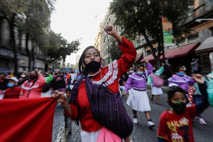 A woman raises her fist during a protest to mark the International Day for the Elimination of Violence against Women, in Mexico City