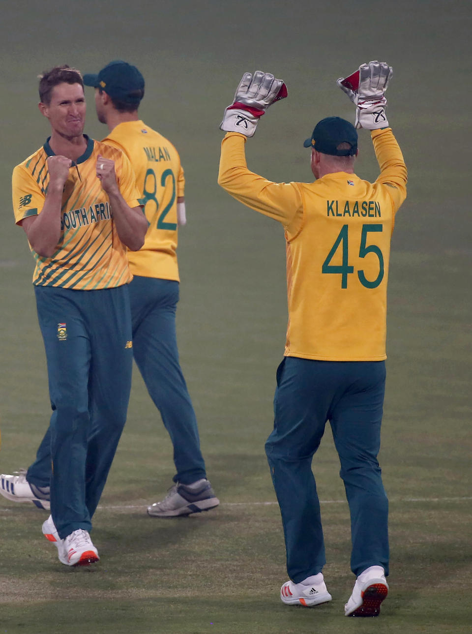 South Africa's Dwaine Pretorius, left, celebrates with teammate after taking the wicket of Pakistan's Babar Azam dismissal during the 2nd Twenty20 cricket match between Pakistan and South Africa at the Gaddafi Stadium, in Lahore, Pakistan, Saturday, Feb. 13, 2021. (AP Photo/K.M. Chaudary)