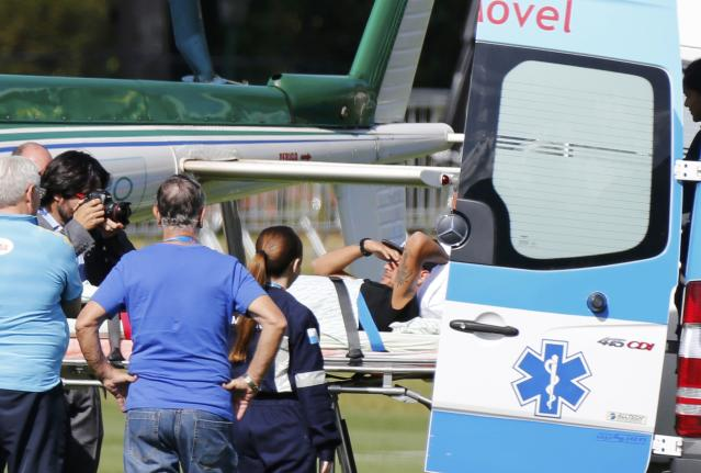Brazil's Neymar is transported from an ambulance to a military helicopter to be airlifted home from Brazil's training camp inTeresopolis near Rio de Janeiro