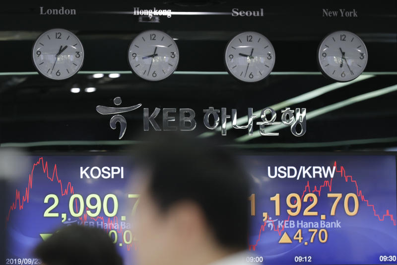 A currency trader watches his computer monitors near screens showing the Korea Composite Stock Price Index (KOSPI), left, and the foreign exchange rate between U.S. dollar and South Korean won at the foreign exchange dealing room in Seoul, South Korea, Monday, Sept. 23, 2019. Stocks got a downbeat start to the week as investors kept a wary eye on tensions with Iran and on signals from China and the U.S. on prospects for a resolution of their tariffs war. (AP Photo/Lee Jin-man)
