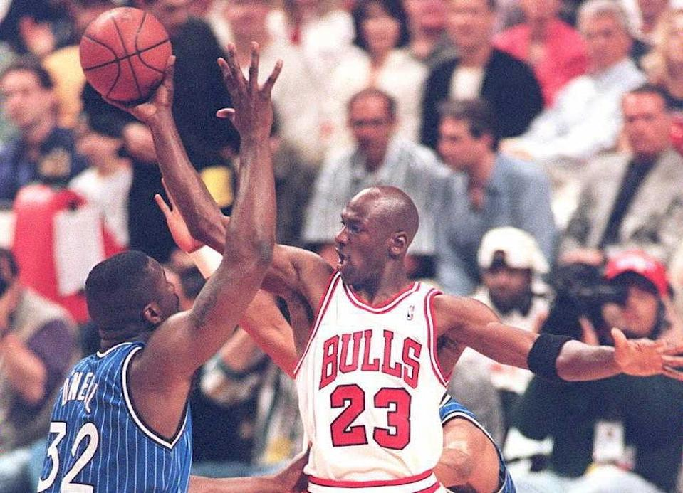 Michael Jordan of the Chicago Bulls (R) passes the ball off under pressure from Orlando Magic center Shaquille O'Neal during an NBA game on May 14, 1995 (AFP Photo/Vincent Laforet)