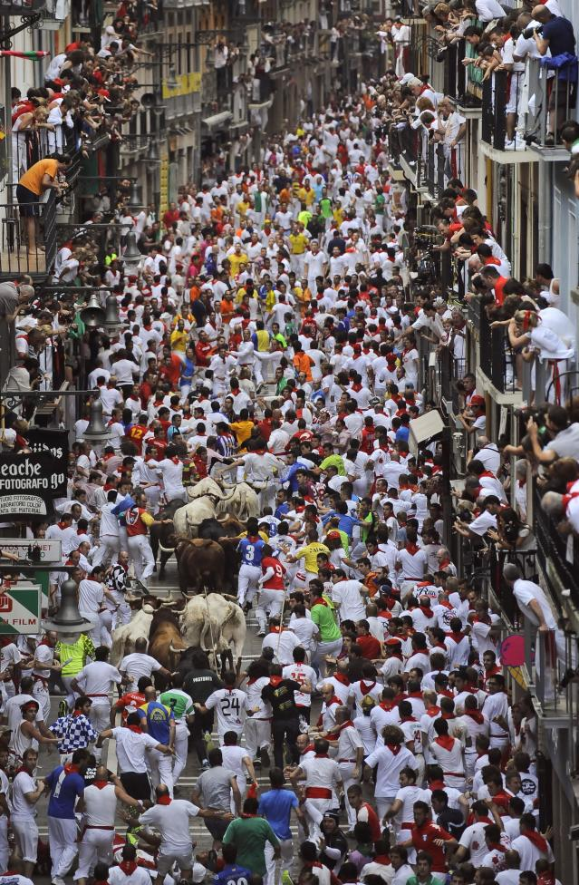 """Runners make their way through the streets with """"El Pilar"""" fighting bulls watched by people from their balconies during the running of the bulls at the San Fermin festival, in Pamplona, Spain, Friday, July 12, 2013. Revelers from around the world arrive to Pamplona every year to take part in some of the eight days of the running of the bulls glorified by Ernest Hemingway's 1926 novel """"The Sun Also Rises."""" (AP Photo/Alvaro Barrientos)"""