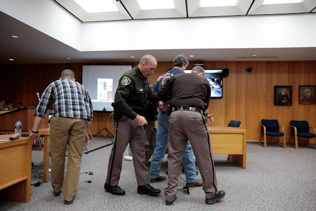 Randall Margraves is removed after he lunged at Larry Nassar (not seen) a former team USA Gymnastics doctor who pleaded guilty in November 2017 to sexual assault charges, during victim statements of his sentencing in the Eaton County Circuit Court in Charlotte, Michigan, U.S., February 2, 2018. Picture 10 of 10 in series. REUTERS/Rebecca Cook