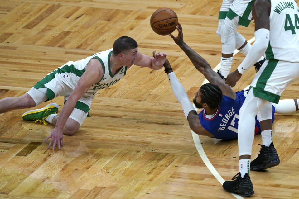 LA Clippers guard Paul George (13) passes the ball after a floor scramble against Boston Celtics guard Payton Pritchard, left, in the second quarter of an NBA basketball game, Tuesday, March 2, 2021, in Boston. (AP Photo/Elise Amendola)