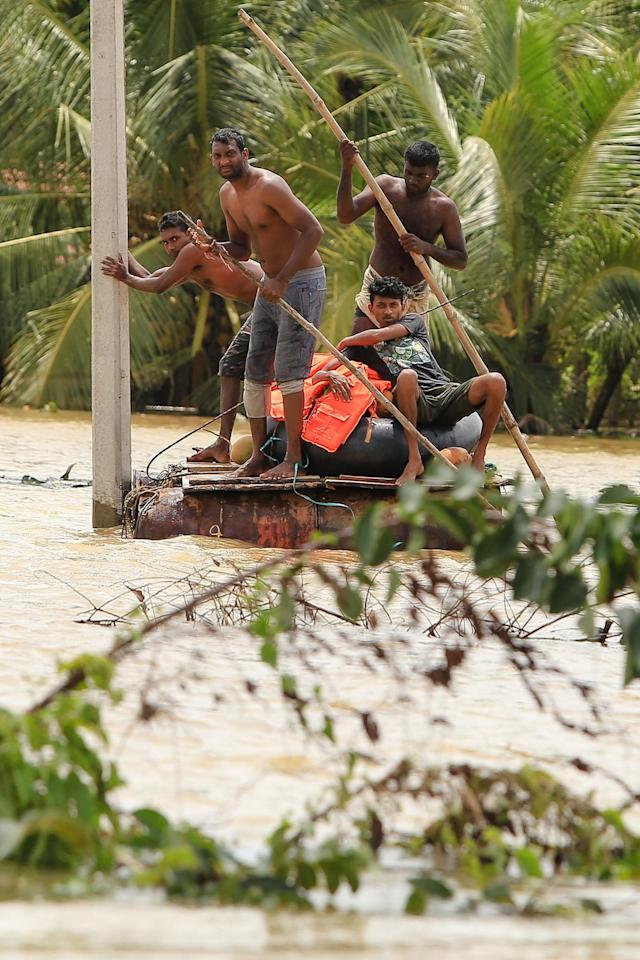 <p>Sri Lankan men row a makeshift raft on a flooded road in Godagama, Matara, Sri Lanka, May 30, 2017. (Tharaka Basnayaka/NurPhoto via Getty Images) </p>
