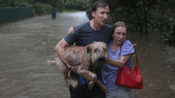 PHOTO: Naomi Coto carries Simba on her shoulders as they evacuate their home after the area was inundated with flooding from Hurricane Harvey, Aug. 27, 2017, in Houston.  (Joe Raedle/Getty Images)