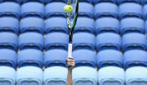 FILE - In this Feb. 14, 2021, file photo, a player hits an overhead shot in front of empty seats during a fourth round match at the Australian Open tennis championships in Melbourne, Australia. Current and former tennis players say they think athletes in their sport might be particularly prone to issues such as stress, anxiety and depression. (AP Photo/Andy Brownbill, File)