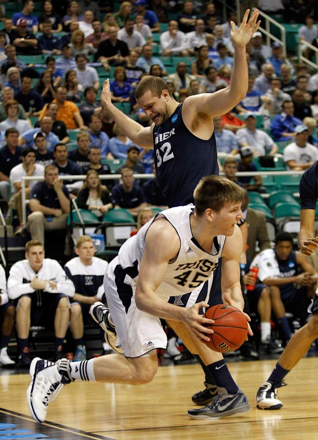 GREENSBORO, NC - MARCH 16: Jack Cooley #45 of the Notre Dame Fighting Irish attempts to get passes Kenny Frease #32 of the Xavier Musketeers in the first half during the second round of the 2012 NCAA Men's Basketball Tournament at Greensboro Coliseum on March 16, 2012 in Greensboro, North Carolina. (Photo by Streeter Lecka/Getty Images)