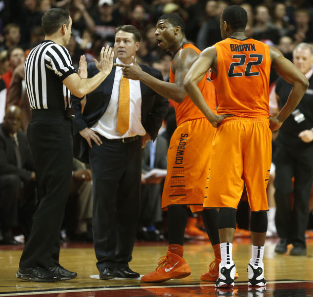 Oklahoma State head coach Travis Ford, center, Marcus Smart and Markel Brown(22) speak to the referee after Smart shoved a fan during a NCAA college basketball game in Lubbock, Texas, Saturday, Feb, 8, 2014. (AP Photo/Lubbock Avalanche-Journal, Tori Eichberger) ALL LOCAL TV OUT
